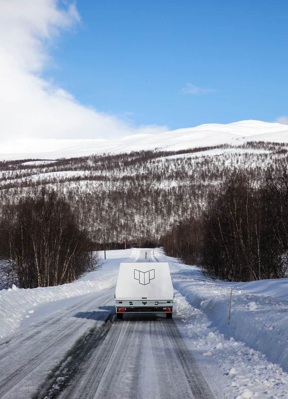4P-släp på en tom väg i norrländska landskap