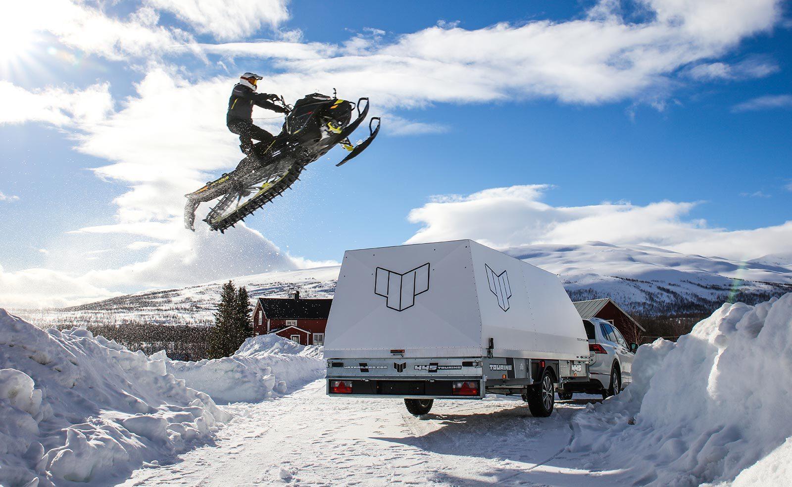 Skoter hoppar över ett 4P-släp i ett snöklätt landskap