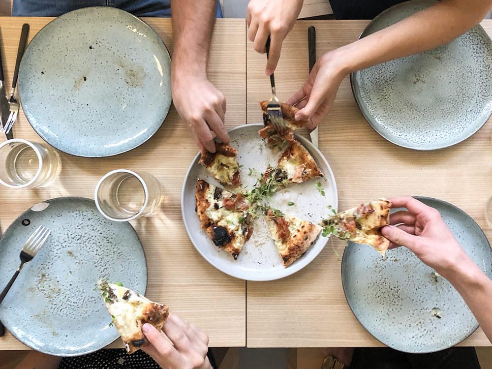Händer som tar gourmetpizza