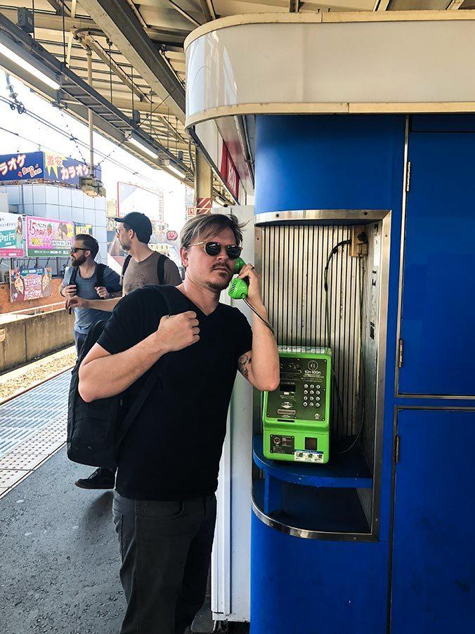 Christian pratar i telefon på tågstation